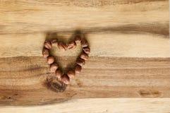 Corazón hecho de avellanas en la madera imagen de archivo