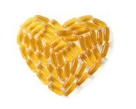 Corazón hecho de cápsulas del aceite de pescado fotografía de archivo libre de regalías