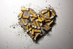Corazón hecho de cigarrillos ahumados y de la ceniza Fotografía de archivo