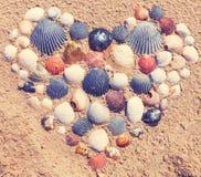 Corazón hecho de conchas marinas en la playa Fotos de archivo libres de regalías