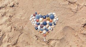 Corazón hecho de conchas marinas en la playa Fotografía de archivo libre de regalías