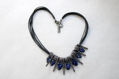Corazón hecho de la joyería femenina, collares con los hilos negros, joyas azules, diamantes, diamantes en la forma de un corazón imágenes de archivo libres de regalías