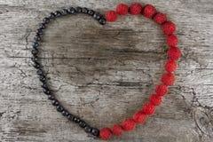 Corazón hecho de las frambuesas y de los arándanos frescos en fondo de madera Nutrición sana Imagen de archivo libre de regalías
