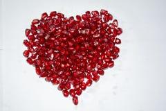 Corazón hecho de las semillas jugosas rojas de la granada con el fondo blanco imagenes de archivo