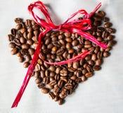 Corazón hecho de los granos de café en el fondo blanco fotos de archivo
