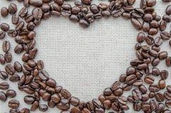 Corazón hecho de los granos de café en el saco texturizado Fotos de archivo
