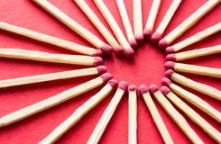Corazón hecho de partidos en fondo rojo Amor Imagenes de archivo
