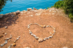 Corazón hecho de piedras en la tierra roja por el mar azul Imagen de archivo libre de regalías