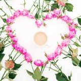 Corazón hecho de rosas y de la taza de café rosadas en el fondo blanco Endecha plana, visión superior Fondo del `s de la tarjeta  Fotografía de archivo libre de regalías