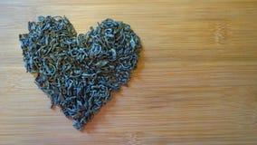 Corazón hecho de té verde en textura de bambú de madera fotos de archivo