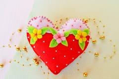 Corazón hecho a mano del fieltro - símbolo del día de tarjetas del día de San Valentín, juguete del fieltro en el fondo blanco Imágenes de archivo libres de regalías