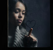 Corazón hermoso del dibujo de la muchacha en ventana mojada Imagenes de archivo
