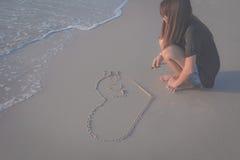 Corazón hermoso del dibujo de la mujer en la arena Imágenes de archivo libres de regalías