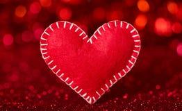 Corazón hermoso hecho a mano fuera del fieltro en fondo brillante foto de archivo