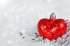 Corazón leído que brilla con los copos de nieve Imágenes de archivo libres de regalías