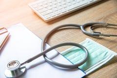 corazón médico del control del estetoscopio cerca de un ordenador portátil en una tabla de madera imagenes de archivo