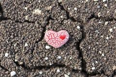 Corazón manchado rojo en suelo seco imagenes de archivo