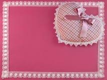 Corazón modelado en color de rosa con una frontera de encaje Foto de archivo