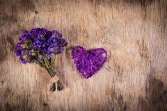 Corazón púrpura y ramo de mimbre de flores secadas en un viejo fondo de madera Imagen de archivo libre de regalías