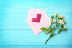 Corazón plástico en sobre y rosas fotografía de archivo