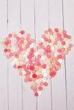 Corazón presentado de los botones en una tabla de madera del fondo blanco Fotos de archivo
