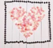 Corazón presentado de los botones en una tabla de madera del fondo blanco Foto de archivo libre de regalías
