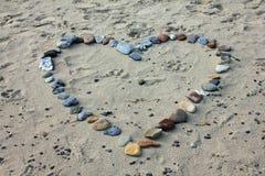 Corazón, presentado de pequeñas piedras del guijarro en la arena gris, de un símbolo del amor y de una confesión de la lealtad Fotos de archivo