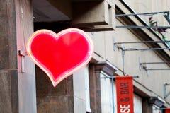 Corazón que brilla intensamente en la fachada del edificio imágenes de archivo libres de regalías