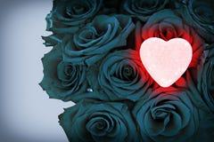 Corazón que brilla intensamente rosado en el ramo azul de rosas Fotografía de archivo