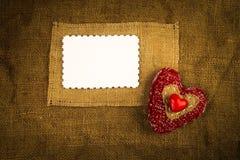 Corazón que hace punto en la harpillera Fotos de archivo