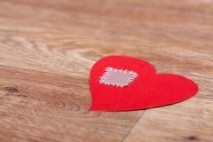 Corazón quebrado perdido en fondo de madera del suelo Imagen de archivo libre de regalías
