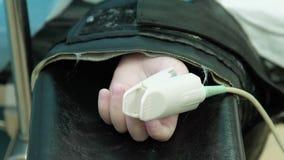 Corazón Rate Sensor en el brazo del paciente en la mesa de operaciones bajo anestesia almacen de video