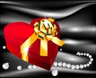 Corazón rojo con el arco de oro en un fondo de la seda Foto de archivo libre de regalías