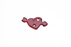 Corazón rojo con la flecha hecha de la jalea en un fondo blanco Foto de archivo