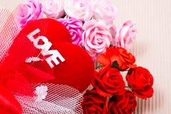 Corazón rojo con palabra y las rosas del amor imagenes de archivo
