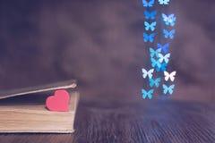 Corazón rojo con un libro viejo en la tabla y un bokeh del fondo hecho de mariposas Día del `s de la tarjeta del día de San Valen Foto de archivo
