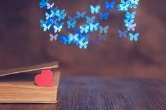 Corazón rojo con un libro y un fondo hermoso de mariposas Fotografía de archivo