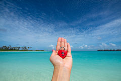 Corazón rojo con una cerradura en la playa tropical en la mano de la mujer Fotos de archivo