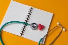 Corazón rojo, cuaderno y un estetoscopio Imágenes de archivo libres de regalías