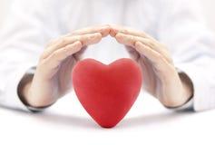 Corazón rojo cubierto por las manos foto de archivo