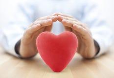 Corazón rojo cubierto por las manos foto de archivo libre de regalías