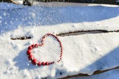 Corazón rojo de gotas en fondo de madera y de la nieve Día del `s de la tarjeta del día de San Valentín Foto de archivo libre de regalías