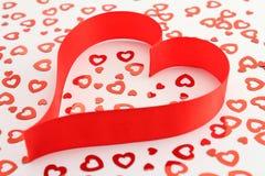 Corazón rojo de la cinta del satén con confeti en forma de corazón Imagenes de archivo