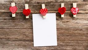 Corazón rojo de la pinza con el blanco de papel Foto de archivo