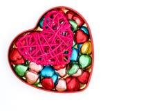corazón rojo de la rota y caramelos de chocolate en forma de corazón imágenes de archivo libres de regalías