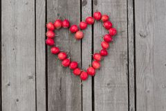 Corazón rojo de las bayas del espino en un fondo de madera Foto de archivo