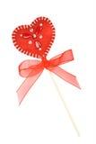 Corazón rojo de las materias textiles con los granos como lollipop Foto de archivo libre de regalías