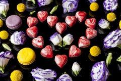 Corazón rojo de los chocolates rodeado con las flores del lado en negro Fotografía de archivo
