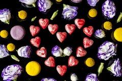 Corazón rojo de los chocolates rodeado con las flores desde arriba en negro Foto de archivo