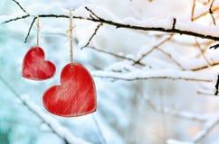 Corazón rojo de madera en rama de árbol nevosa en invierno Foto de archivo